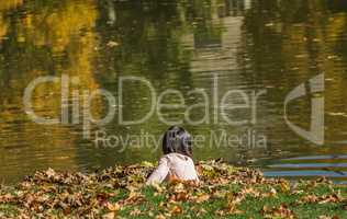 Child Plays With Leaves On A Pond In Autumn