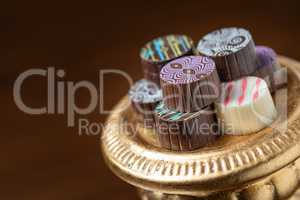 Artisan Fine Chocolate Candy On Gold Pillar Serving Dish