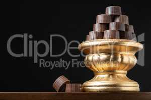 Stack of Fine Chocolates On Golden Pillar Dish With Dark Backgro