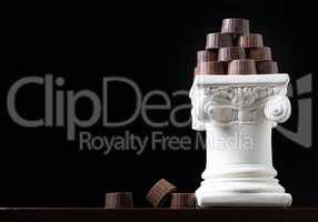 Stack of Fine Artisan Chocolates Stacked On White Pillar Column