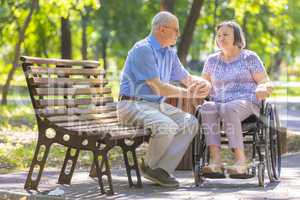 Elderly man strengthens his wife in the wheelchair