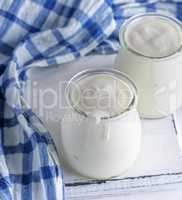 glass jars with homemade yogurt on a white wooden board