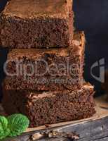 square pieces of baked brownie lie in a pile