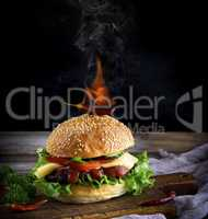 classic burger with a meatball, cheese and vegetables, on top of