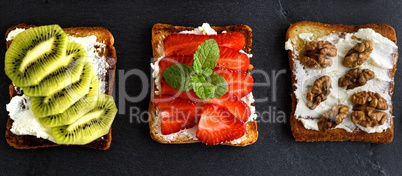 three toasts with mild cottage cheese, strawberries, kiwi and nu
