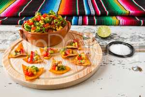 Nachos chips and vegetables in an earthenware bowl and tequila w