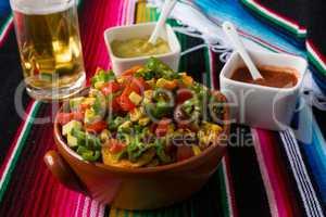 Nachos salad hot sauces and beer
