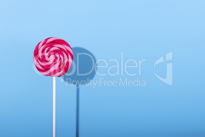 Pink Lolipop candy with shadow on pastel blue background