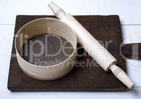brown wooden kitchen cutting board, rolling pin and sieve
