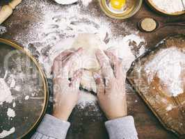 two female hands knead a dough of white wheat flour