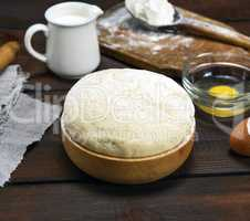 dough made from white wheat flour in a wooden bowl