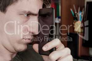 guy looks at the screen of a black smartphone, through the refle