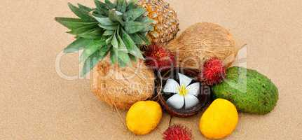 Set of tropical fruits on a sandy beach. Wide photo.