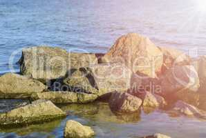 Large stones in sea water on a summer day