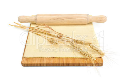 Wheat ears, rolled dough and rolling pin isolated on white backg