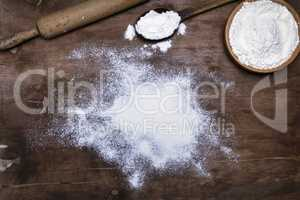 scattered white wheat flour on a brown wooden surface