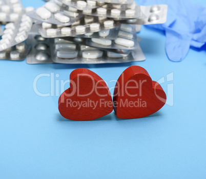 two red wooden hearts on a blue background, behind a stack of pi