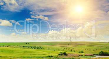 Hilly green field, windmill and sun on blue sky background. Wide