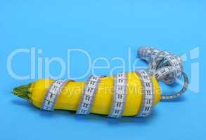 yellow raw zucchini wrapped in a measuring tape