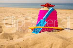 bucket and shovel with sea star on a sunny beach