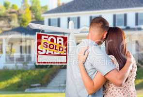 Military Couple Looking At House with Sold For Sale Real Estate