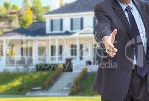 Male Agent Reaching for Hand Shake in Front of Beautiful New Hou