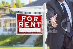 Male Agent Reaching for Hand Shake in Front of For Rent Sign and