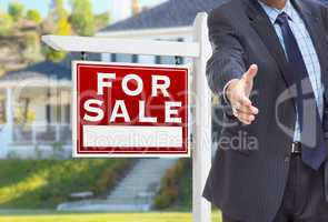 Male Agent Reaching for Hand Shake in Front of For Sale Sign and
