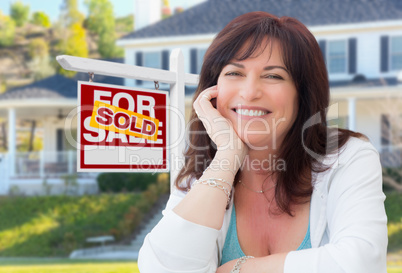 Middle Aged Woman In Front of House with Sold For Sale Real Esta
