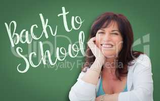 Back To School Written On Green Chalkboard Behind Smiling Middle