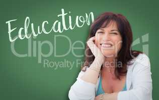 Education Written On Green Chalkboard Behind Smiling Middle Aged