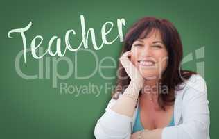 Teacher Written On Green Chalkboard Behind Smiling Middle Aged W