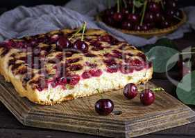 piece of biscuit cherry pie on a brown wooden board