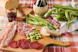 Chopping board of cold meats and broad bean