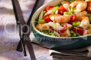 Close up of salad of shrimps and chopsticks