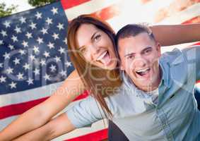 Military Couple Piggy Riding In Front of American Flag