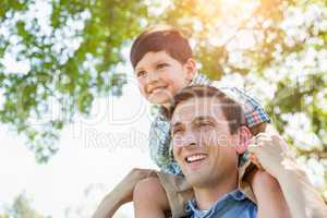 Mixed Race Father and Son Playing Piggyback Together in the Park