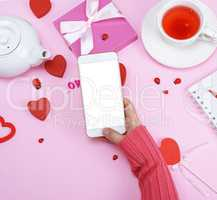 right female hand in a pink sweater is holding a white smartphon