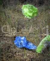 empty plastic bags fly through the green meadow
