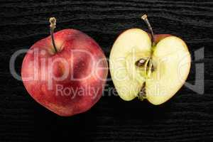Fresh raw apple red delicious on black wood