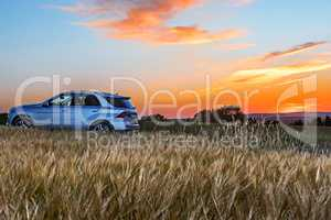 Moody sunset with cornfield and car