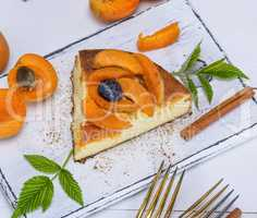 piece of cheesecake with apricots on a white wooden board