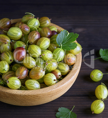 round wooden bowl with green gooseberries