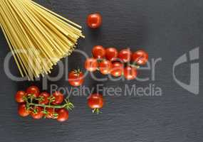 raw Italian long pasta and ripe red cherry tomatoes
