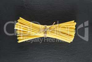 raw spaghetti tied with a rope on a black background