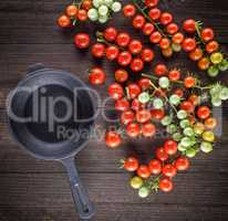 empty black cast-iron frying pan and red cherry tomatoes