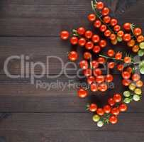 ripe red cherry tomatoes on a brown wooden board