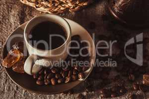 cup of coffee with beans, dark candy sugar and pot
