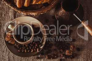 top view cup of coffee with beans, dark candy sugar, pot, basket and cake