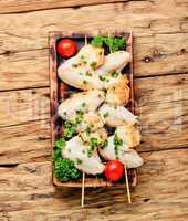 Raw chicken kebab on stick